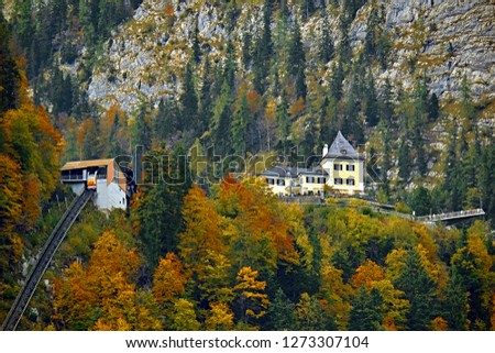 Beautiful aerial fall view of cable car ropeway funicular in austrian alps. Red cable railway car in the mountains by resort village Hallstatt, Salzkammergut, Austria, Alps. #1273307104