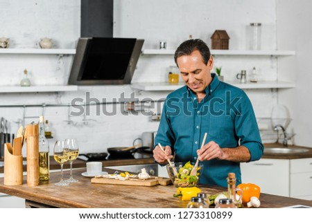 handsome mature man cooking in kitchen #1273310899