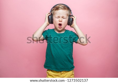 Stylish teen boy listening music in headphones and singing against pink background. School child listening loud music in wireless earphones and dancing.  #1273502137