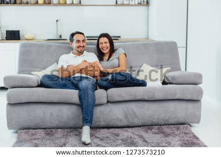 Husband and wife sitting on a sofa watching a movie #1273573210