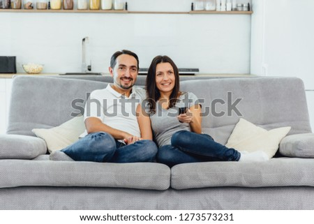 Husband and wife sitting on a sofa watching a movie #1273573231