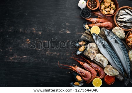 Seafood. Fresh fish, shrimp, oysters and caviar on a black wooden background. Top view. Free copy space. #1273644040