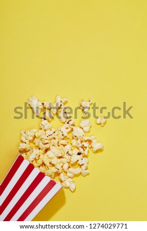Full of popcorn in classic striped box on color background #1274029771