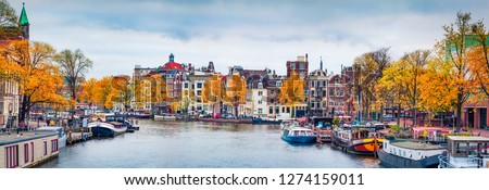Panoramic autumn view of Amsterdam city. Famous Dutch channels and great cityscape. Gloomy morning scene of Netherlands, Europe. Traveling concept background. #1274159011