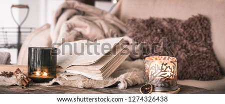 still life home atmosphere in the interior with a book and candles, on the background of cozy bedspreads, home decor elements, the concept of comfort and coziness Royalty-Free Stock Photo #1274326438