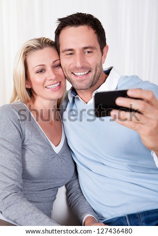 Beautiful smiing young couple photographing themselves on a mobile or smartphone posing close together with his arm around her #127436480