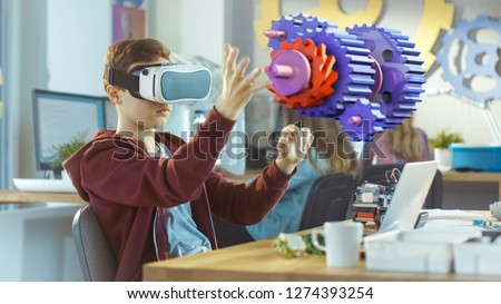 In a Computer Science Class Boy Wearing Virtual Reality Headset Works in Interactive 3D Environment. Mechanical Modeling Project of Connecting Gears with Augmented Reality Software. #1274393254