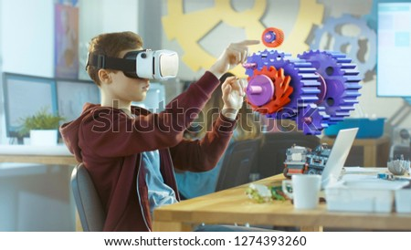 In a Computer Science Class Boy Wearing Virtual Reality Headset Works in Interactive 3D Environment. Mechanical Modeling Project of Connecting Gears with Augmented Reality Software. #1274393260