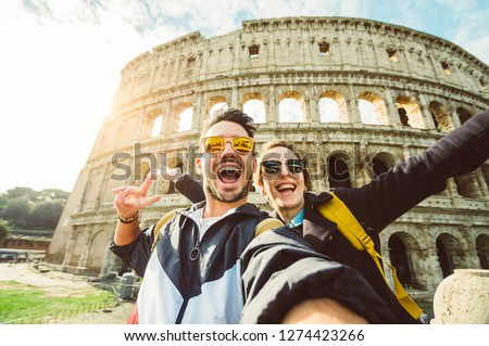 Happy caucasian couple is taking a selfie smiling at the camera in front of the colosseum in Rome #1274423266