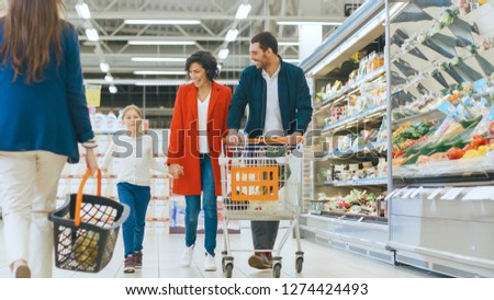 At the Supermarket: Happy Family of Three, Holding Hands, Walks Through Fresh Produce Section of the Store. Father, Mother and Daughter Having Fun Time Shopping. #1274424493
