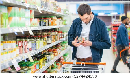 At the Supermarket: Handsome Man Uses Smartphone and Looks at Nutritional Value of the Canned Goods. He's Standing with Shopping Cart in Canned Goods Section. #1274424598