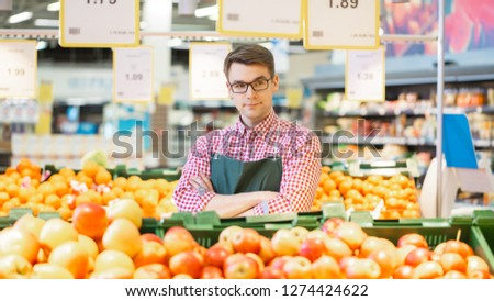 At the Supermarket: Portrait Of the Handsome Stock Clerk Wearing Apron, Arranging Organic Fruits and Vegetables, He Smiles and Crosses Arms. Friendly, Efficient Worker at the Store. #1274424622