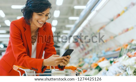 At the Supermarket: Beautiful Smiling Woman Uses Smartphone, Leans on Shopping Cart in the Fresh Produce Section of the Store. In the Big Mall Woman Browsing In Internet on Her Mobile Phone. #1274425126