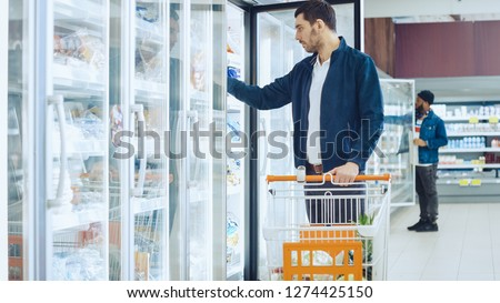 At the Supermarket: Handsome Man Pushes Shopping Card and Browses for Products in the Frozen Goods Section. Man Opens the Fridge Door and Takes Frozen Vegetables. Other Customer Shopping in Background #1274425150