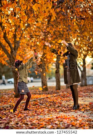 Vertical photo,  happy beautiful little girl with mather throw up  autumnal leafage, in park
