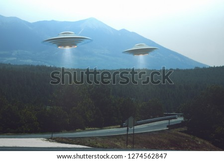 Unidentified flying object. Two UFOs flying over a road among the trees. 3D illustration. #1274562847
