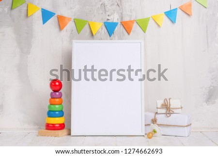 Children's toys, with a white frame The frame on a light background of the wall with children's signs, for design, layout. Baby shower