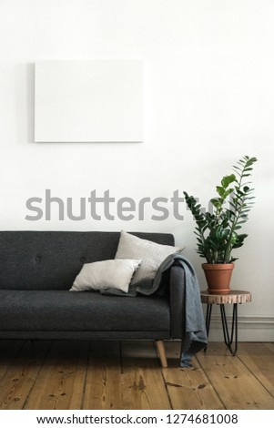 Interior poster painting mock up with empty canvas hanging on white wall, room with sofa and green plant. Interior design photography with copy space