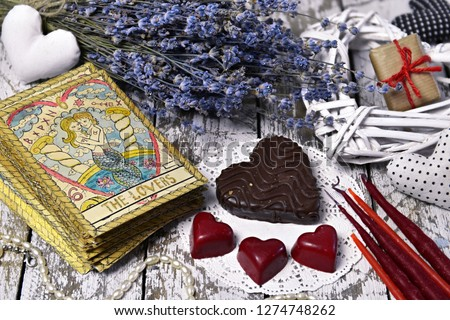 "Tarot card Lovers, chocolate candies, heart and love symbols. The English title on the card ""Lovers"" means the word ""lovers"". Romantic vintage valentine's day and wedding background #1274748262"