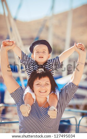 Beautiful young family of two walking along wooden jetty/ Woman with son on pier #127495034