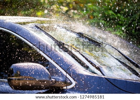 wing mirror and car windshield with rain drops and frameless wiper blade closeup Royalty-Free Stock Photo #1274985181