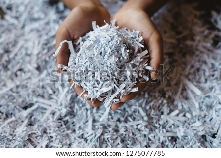 hand showing heap of shredded paper. Concept of recycle and office work of confidential #1275077785