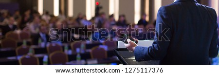 Presenter Giving Presentation to Audience. Speaker During Speech in Conference Hall Auditorium. Defocused Blurred Meeting People. Corporate Lecturer on Stage. #1275117376