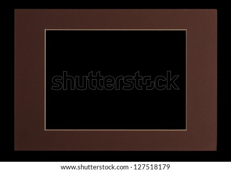 Brown matte cardboard picture frame / passepartout, cut out over black background.