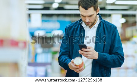 At the Supermarket: Handsome Man Uses Smartphone to Check Nutritional Value of the Canned Goods and Buy it. He's Standing with Shopping Cart in Canned Goods Section.