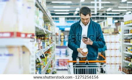 At the Supermarket: Handsome Man Uses Smartphone and Takes Picture of the Can of Goods. He's Standing with Shopping Cart in Canned Goods Section.
