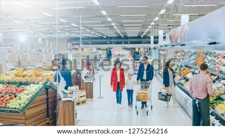 At the Supermarket: Happy Family of Three, Holding Hands, Walks Through Fresh Produce Section of the Store. Father, Mother and Daughter Having Fun Time Shopping. High Angle Panoramic Shot. #1275256216