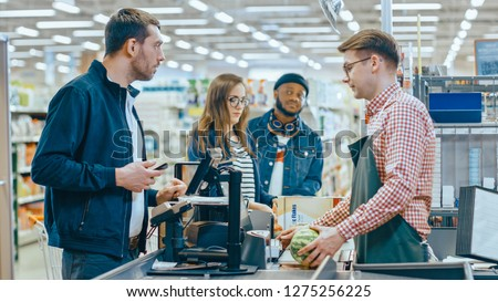 At the Supermarket: Checkout Counter Customer Pays with Smartphone for His Items. Big Shopping Mall with Friendly Cashier, Small Lines and Modern Wireless Paying Terminal System. #1275256225