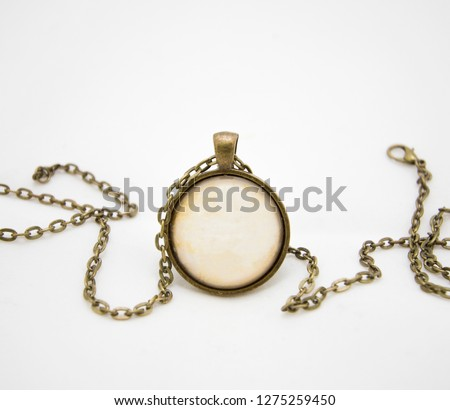 Gold pendant on a chain. Pendant upright. Round neck pendant. Decoration for inscriptions. Box for text in the pendant. Yellow metal. Retro paper in the decoration. Gold chain on a light background. #1275259450