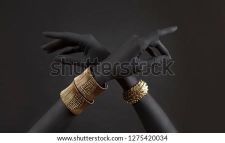 Black woman's hands with gold jewelry. Oriental Bracelets on a black painted hand. Gold Jewelry and luxury accessories on black background closeup. High Fashion art concept  #1275420034