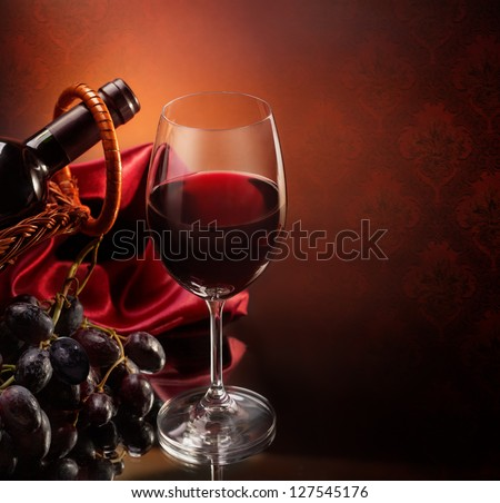 Bottle with bunch of grapes and wineglass of red wine #127545176