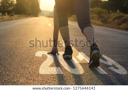 Healthy way of life new year concept. goals and plans, Healthcare and medical. Woman in sports wear running start to goals new year 2019 on the road in sunset background. #1275646141
