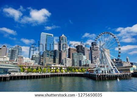 Seattle Ferris wheel, skyline and waterfront sunny day with blue sky and clouds.  Royalty-Free Stock Photo #1275650035