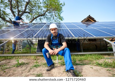 Portrait of male engineer technician with electrical screwdriver looking in camera sitting in front of almost finished high exterior solar panel photo voltaic system with team of workers on platform. #1275720460