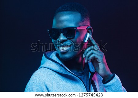 Neon portrait of young african man listening music with wireless earphones #1275745423
