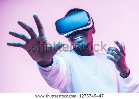 African american man in vr glasses, playing video games with virtual reality headset, trying to touch something with hand #1275745447