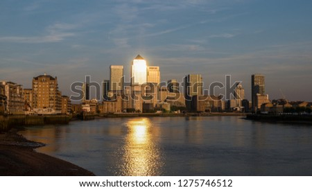 View of Canary Wharf buildings at sunset clouds and sun reflections in London, United Kingdom, Europe #1275746512
