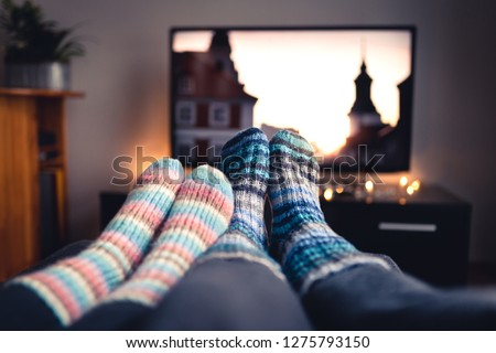 Couple with socks and woolen stockings watching movies or series on tv in winter. Woman and man sitting or lying together on sofa couch in home living room using online streaming service in television #1275793150