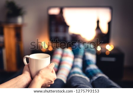 Couple drinking tea, hot chocolate, eggnog or mulled wine and watching tv in warm cozy woolen socks in winter. Woman holding cup of morning coffee in home living room. Sick people with flu or fever. #1275793153