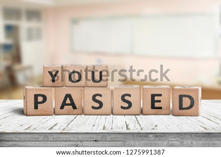 You passed sign for quiz and education purposes on a wooden desk in a bright class room #1275991387