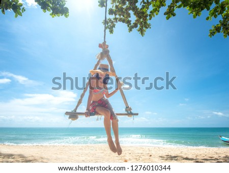 woman enjoy happy the nature of the sea beach by sitting on the wooden swing tie under the shadow of the plam tree, long weekend and vacation holidays spent slow life on the beach - Image
