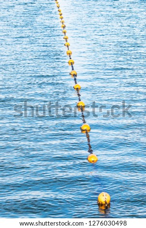 Yellow float floats on a rope floating in the sea #1276030498