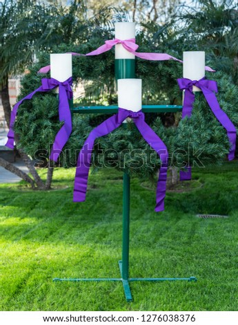 Garden Grove, California, USA - December 13, 2018: Crystal Christ Cathedral. Closeup of the Advent Wreath in the garden. Green backgroound, four white candles, purple and pink ribbons. #1276038376