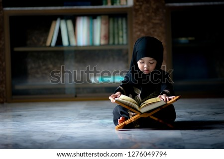 Asian Indonesian Muslim kid is reading the Quran. The Quran is indicated as the guided book for all Muslim and it is direction  to be on the heaven of God.Mosque,Islam,religion and knowledge concept. #1276049794