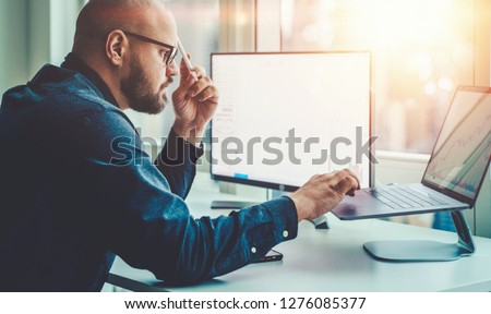 Businessman study financial market to calculate possible risks and profits. Male economist accounting money and research statistics graphs on laptop computer at office desktop. Quotations on exchange #1276085377