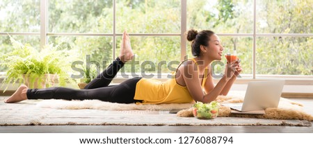 Healthy Asian woman lying on the floor eating salad looking relaxed and comfortable #1276088794